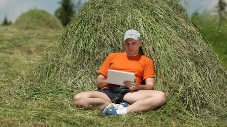 hay cock : Man with tablet PC sits near haystack. Man in orange t-shirt uses tablet PC. Male with white tablet computer. Sportsman with Tablet PC lies on hayrick