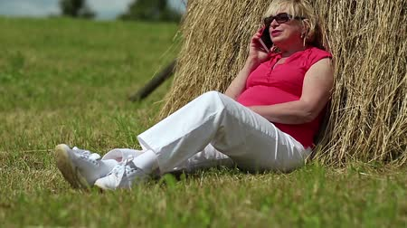 hay cock : Senior woman sits near haystack and communicates via mobile phone. Blonde woman with smartphone. Female with smartphone Stock Footage