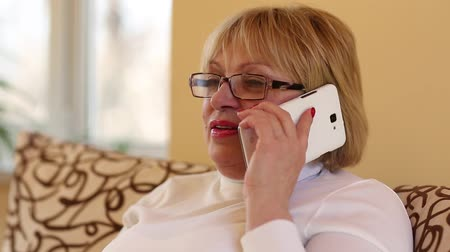 wistful : Woman communicates via smartphone. Blonde woman with white smartphone. Female talks on the cell phone Stock Footage