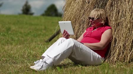 hay cock : Senior blonde woman sits on a green grass near haystack and communicates via tablet computer. Female with tablet computer. Businesswoman with Tablet PC communicates through skype Stock Footage