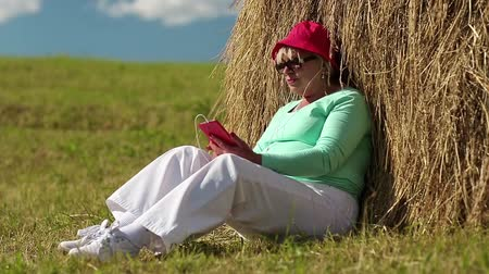 hay cock : Woman in red cap with red smartphone sits near hayrick and listens to music. Senior woman with red smartphone sits on the grass and listens to music. Businesswoman with mobile phone in the meadow Stock Footage