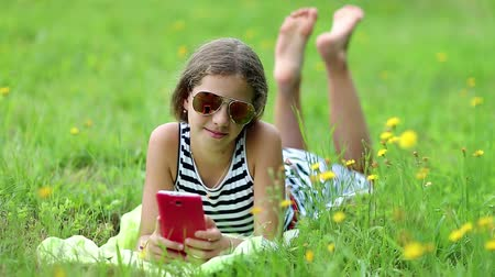 otlak : Attractive girl in sunglasses with red smartphone lies on the grass. Pretty girl playing the game on his smartphone. Little girl in glasses lies on the green grass and uses cell phone Stok Video