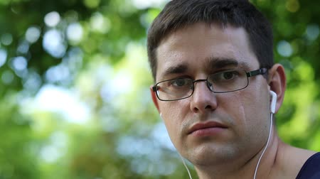 feszült : Man with earphones looks at the camera. Adult man in glasses with a scar on face looks at the camera and smiles. Man with earpieces in city park