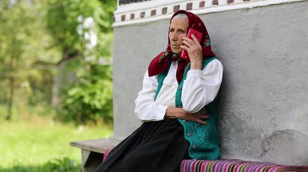 starość : Senior woman sits on bench and talks on mobile phone. Old woman sits on bench near his house and speaks on cell phone. Ukrainian old woman with red smartphone. Female with smartphone