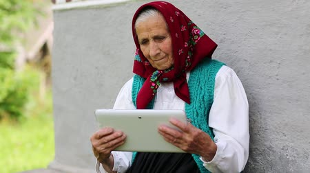 starość : Old woman sits on bench and communicates via tablet computer. Old woman sits on bench near his house and speaks via tablet pc in instant messaging . Ukrainian old woman with white tablet pc. Female with tablet pc