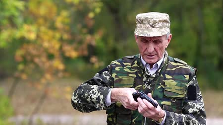 harcias : Soldier in military uniform shoots a revolver. Retired officer at shooting range. Senior man in military uniform shoots a pistol in forest. Man with black gun
