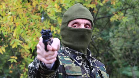 slayer : Man in military uniform and mask with black revolver in hand. Soldier in military uniform aims at a target. Retired officer at shooting range. Senior man in military uniform in forest. Man with gun Stock Footage