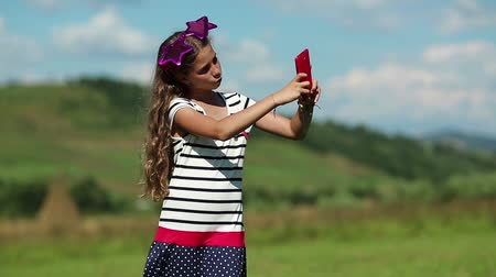 babbler : Beautiful girl stands on the meadow and speaks on cell phone. Attractive girl with big glasses on the head in the shape of stars stands on grassland and speaks on smartphone. Female with smartphone Stock Footage