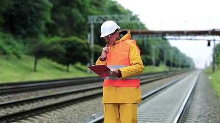 railwayman : Railway worker in yellow uniform and white hard hat with documents in hands. Inspector of railway traffic makes notes in his documents. Railway employee in yellow uniform on railway line