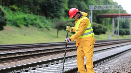 railwayman : Railway worker in yellow uniform with crowbar in hands mends railway line. Railwayman in yellow uniform with crowbar in hands repairs railway track. Workman with metal crowbar on railway track