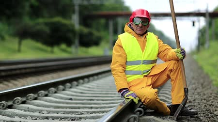 slogger : Railway worker in yellow uniform with shovel in hand sits on railway line. Railwayman in red hard hat sits on rail and looks at the camera. Workman with spade on railway track. Railway construction