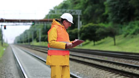 railwayman : Railway worker in yellow uniform with documents. Inspector of railway traffic. Railway employee in yellow uniform on railway line. Inspector of railway traffic makes notes in his documents Stock Footage