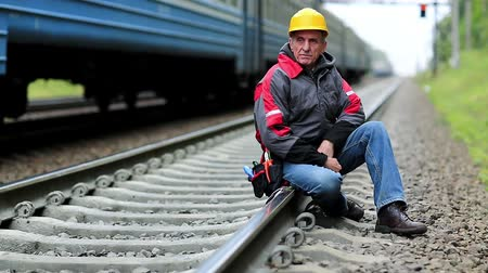 railwayman : Railway worker sits on railway line. Train rides on the railroad. Railwayman in yellow hard hat sits on rail and looks at the camera. Workman on railway track