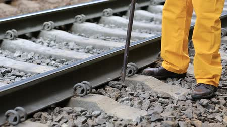 slogger : Railwayman repairs railway line. Railwayman in yellow uniform with crowbar repairs railway track. Workman with metal crowbar on railway track Stock Footage