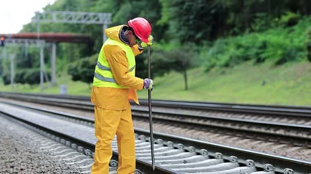 railwayman : Railwayman in yellow uniform with crowbar in hands repairs railway track. Workman with metal crowbar on railway track. Railway worker in yellow uniform with crowbar in hands mends railway line Stock Footage