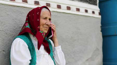 starość : Senior woman sits near grey wall of his house and talks on mobile phone. Old woman sits on bench near his house and speaks on cell phone. Ukrainian old woman with smartphone. Female with smartphone