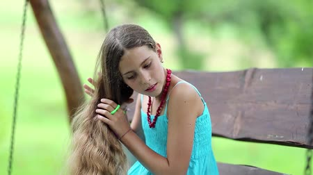 incelik : Attractive girl in blue sundress sits on the bench and combs his long hair. Beautiful girl combs his long hair Stok Video