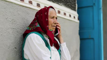 starość : Old woman sits on bench near his house and speaks on cell phone. Ukrainian old woman with red smartphone. Female with smartphone