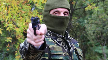 slayer : Man with gun. Man in military uniform and mask with black revolver in hand. Soldier in military uniform aims at a target. Retired officer at shooting range. Senior man in military uniform in forest Stock Footage
