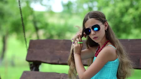 incelik : Beautiful girl braids his long hair. Weave braids for long hair. Girl in blue sundress sits on the swing bench and braids his long hair. Pretty brunette sits on swing bench and braids his hair
