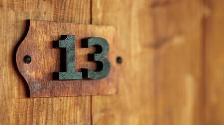 numerology : Hotel room number thirteen. Wooden door of room number 13. House doorplate number thirteen, bakers dozen, seventh Fibonacci number close-up. Triskaidekaphobia - superstitious fear of number thirteen Stock Footage