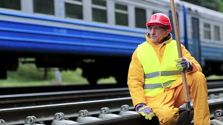 slogger : Railway worker in yellow uniform with shovel in hand sits on railway line. Railwayman in red hard hat sits on rail and looks at the train. Workman with spade on railway track. Railway construction Stock Footage