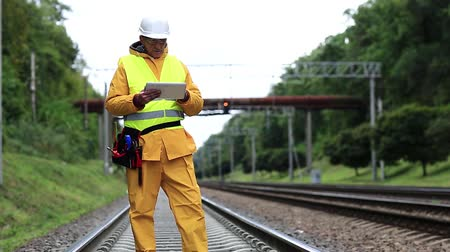 railwayman : Inspector of railway traffic makes notes in tablet computer. Railway employee in yellow uniform on railway line. Railway worker in yellow uniform and white hard hat with tablet pc in hands Stock Footage