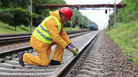 slogger : Railway worker in yellow uniform with level measuring instrument on railway line. Railway man in red hard hat sits on railway tracks and looks at the train. Workman with level measuring instrument Stock Footage