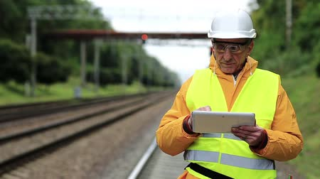 railwayman : Railway worker makes notes in his tablet computer. Railway worker in yellow uniform and white hard hat with tablet pc in hands. Railway employee in yellow uniform on railway line Stock Footage