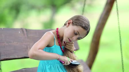 incelik : Attractive girl in blue sundress sits on the bench and combs his long hair. Beautiful girl combs his long hair. Girl with hairbrush sits on bench in garden