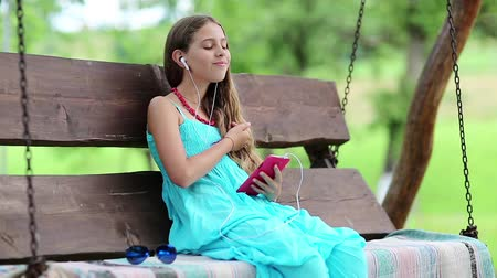 babbler : Beautiful girl in blue dress sits on the swing bench in garden and speaks via red smartphone. Attractive girl with earphones and smartphone communicates through instant messaging. Female with smartphone