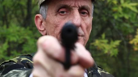 harcias : Man with black gun looks at the camera. Retired officer in military uniform at shooting range. Man holds in hands black revolver