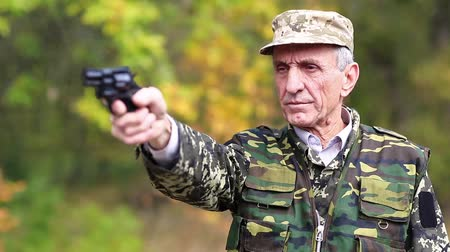 harcias : Retired officer in military uniform shoots a revolver. Man with black gun. Retired officer at shooting range. Senior man in military uniform shoots a pistol in forest