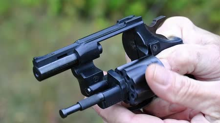 harcias : Man turns cylinder of black revolver. Man with black gun, close up. Man holds in hands black revolver with flobert cartridges