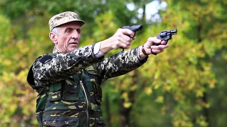 harcias : Soldier in military uniform shoots from two pneumatic handguns. Senior man shoots a two pistols in forest. Soldier in military uniform shoots a revolver. Retired officer at shooting range