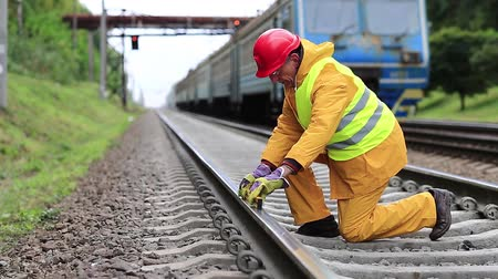 slogger : Railway man in red hard hat sits on railway tracks and looks at the train. Workman with level measuring instrument. Railway worker in yellow uniform with level measuring instrument on railway line Stock Footage