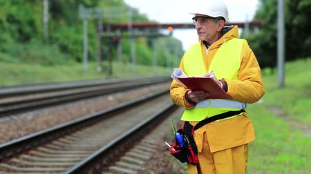 railwayman : Inspector of railway traffic. Railway worker in yellow uniform with documents. Railway employee in yellow uniform on railway line. Inspector of railway traffic makes notes in his documents