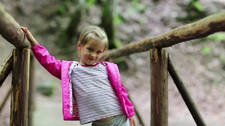 jovial : Funny little girl in pink jacket on the nature. Little girl stands on a wooden bridge and smiles Vídeos