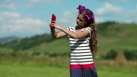 babbler : Pretty girl stands on the meadow and speaks on cell phone. Attractive girl with big glasses on the head in the shape of stars stands on grassland and speaks on smartphone. Female with smartphone