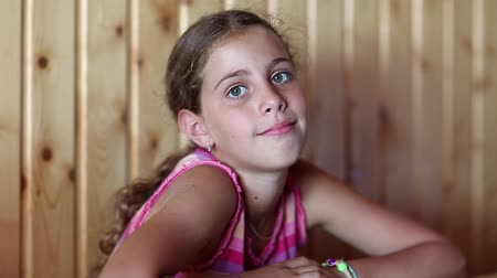 félénk : Pretty girl sits at the table and looks at the camera. Beautiful girl looking at the camera Stock mozgókép
