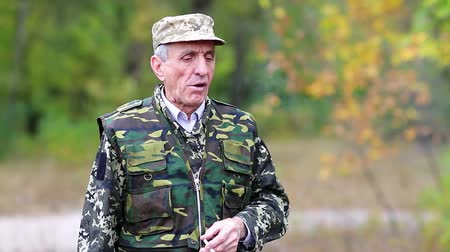 harcias : Senior man in uniform stands on a post in the wood. Man with cigarette. Retired officer smokes a cigarette in the forest. Hunter in the forest. Elderly person in military uniform smokes a cigarette Stock mozgókép