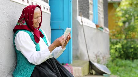 babbler : Old woman sits on bench and communicates via tablet computer. Senior woman sits on bench near his house and speaks via tablet pc . Ukrainian old woman with tablet pc communicates through instant messaging Stock Footage