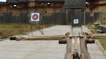 harcias : Crossbow is aimed at a target. Old wooden arbalest and targets at background. Ancient ballista