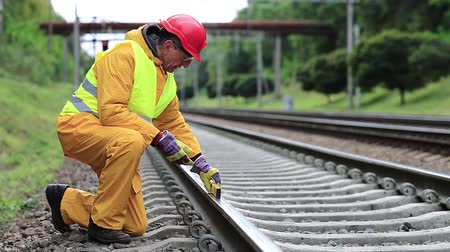 train workers : Railway worker in yellow uniform with level measuring instrument on railway line. Railway man in red hard hat sits on railway tracks and looks at the train. Workman with level measuring instrument Stock Footage