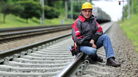railwayman : Railwayman in yellow hard hat sits on rail and looks at the camera. Workman on railway track. Railway worker sits on railway line. Train rides on the railroad