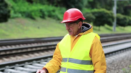railwayman : Railway worker in yellow uniform stands on railway line and smokes. Railway man in red hard hat stands on railway track. Working man with cigarette on railway tracks. Smoke break