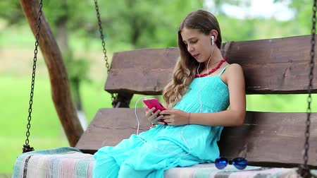 babbler : Beautiful girl in blue dress sits on the swing bench in garden and speaks via red smartphone. Attractive girl with earphones and smartphone communicates through video call. Female with smartphone