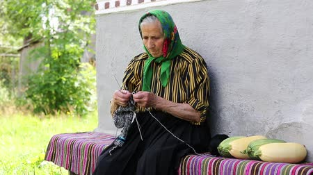 starość : Ukrainian old woman is engaged in knitting. Old woman sits on bench and knits woollen socks. Senior woman in green headscarf sits near his house and knits sock. Female in kerchief knits woollen sock
