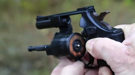 harcias : Man holds in hands black revolver with flobert cartridges. Man turns cylinder of black revolver. Man with black gun, close up Stock mozgókép