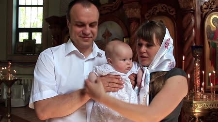 baptismal : Mother and father with baby in orthodox church after christening ceremony